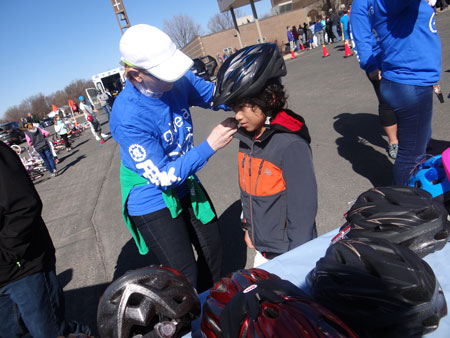 child getting fitted for bike helmet