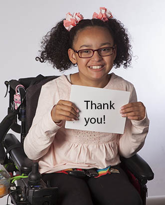 Little girl in wheelchair holding thank you card