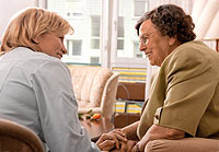 A volunteer sits and talks with a hospice patient