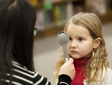 Volunteer tests a child's vision during E.Y.E. vision screening at a public school