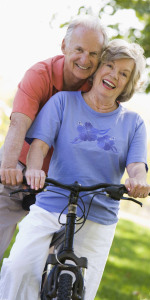 A middle-aged couple smiles as they bike through Fridley, Minnesota.