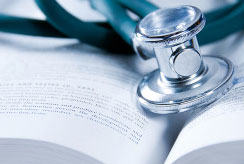 A doctor's stethoscope lays atop a large book that contains federal health reform legislation