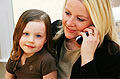 woman on phone with daughter in her lap