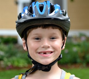 A boy who just lost his front took, proudly shows how to wear a bike helmet correctly.