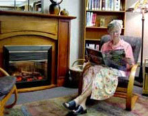 A woman reads about cancer while sitting in a rocking chair next to a fireplace at the Mercy Hospital Cancer Resource center