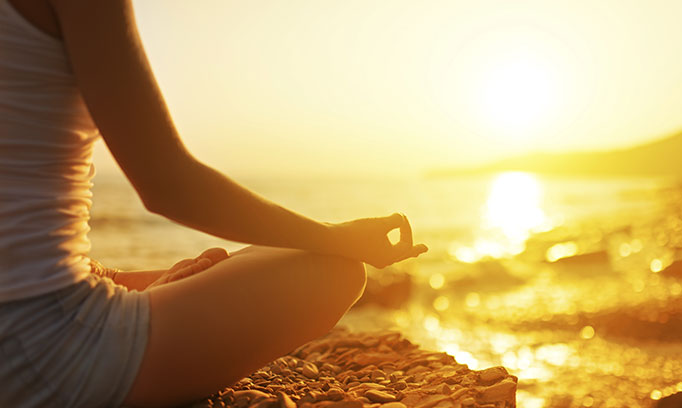 person meditating on beach to alleviate daily stress
