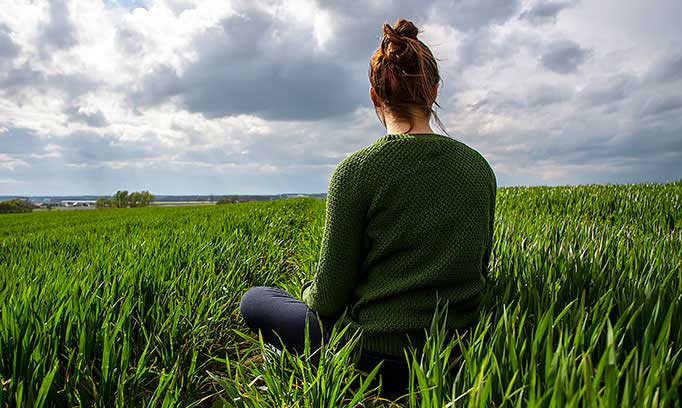 woman sitting in field, relaxing to beat heart disease