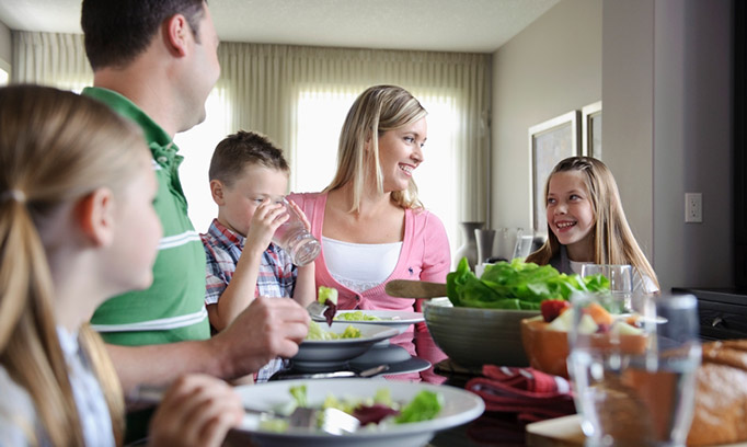 family at dinner table trying to start healthy habits