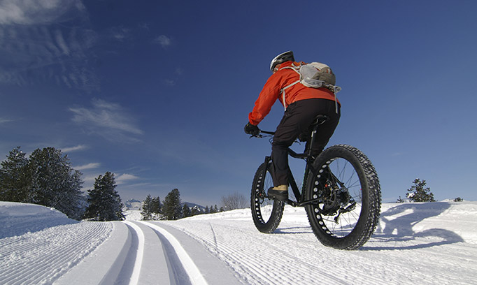 person riding bike on snow, winter workouts