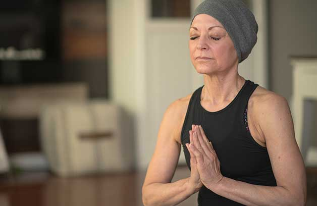 Senior woman with cancer, meditating while seated on the floor. She's wearing a gray head scarf and a black leotard.