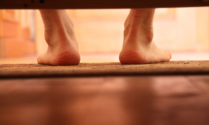 Bare feet on the floor as man steps out of bed, an example when you might hear cracking and popping noises in joints.