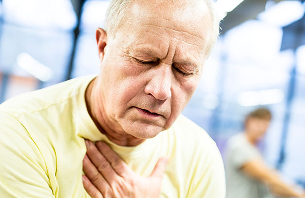 Man holding neck and chest area because of heartburn