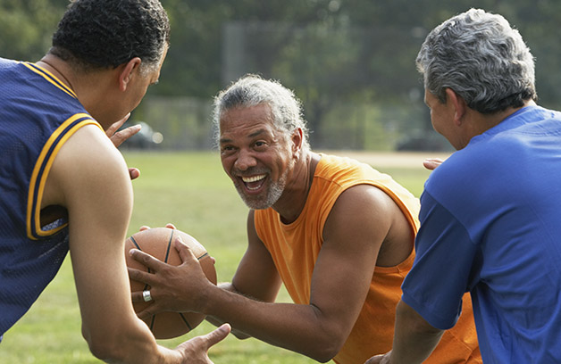 Three older men playing football in a park.