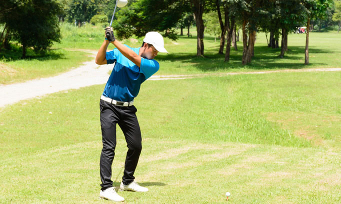 Golfer prepares to swing club after stretches to prevent back injury