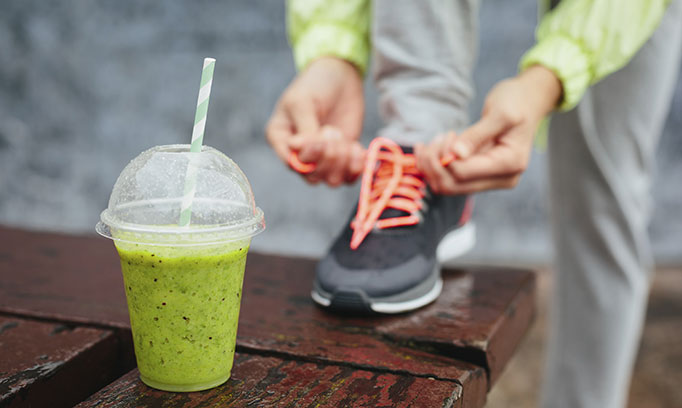 Woman with pre-workout smoothie prepares for a run