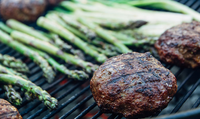 burgers and asparagus cooking on a grill