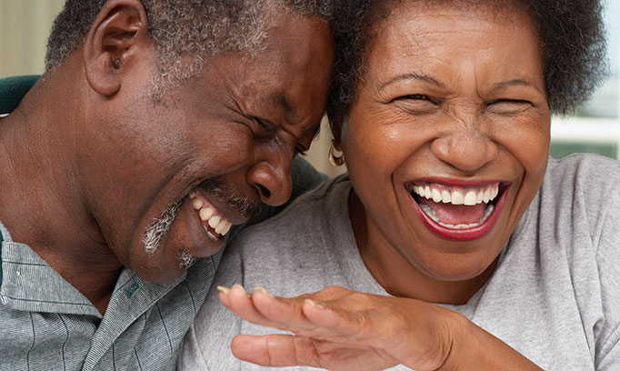 Middle aged man and woman laughing over stress incontinence, perhaps?