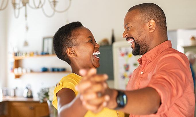 Laughing middle-aged African American couple enjoy staying fit by dancing together in their kitchen.