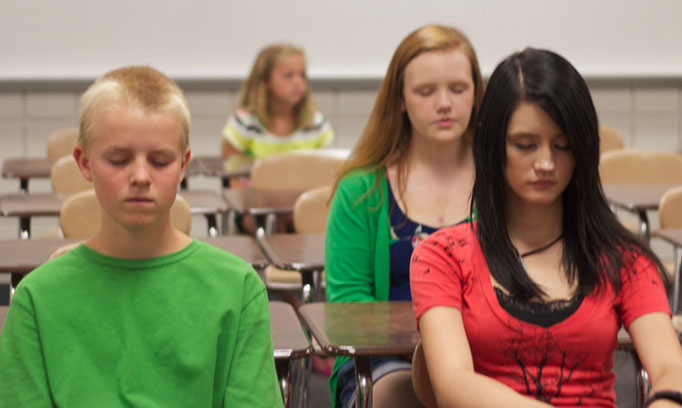 Kids in a classroom practice guided imagery as a way to reduce stress