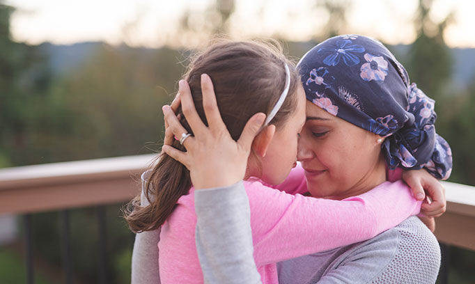 Two women hug, one appears to be undergoing cancer treatment  as she's wearing a blue bandanna on her head