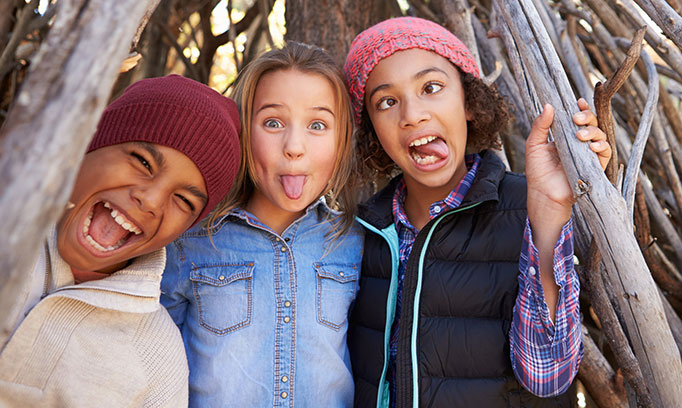 Three middle school kids who have been vaccinated for HPV act goofy for the camera