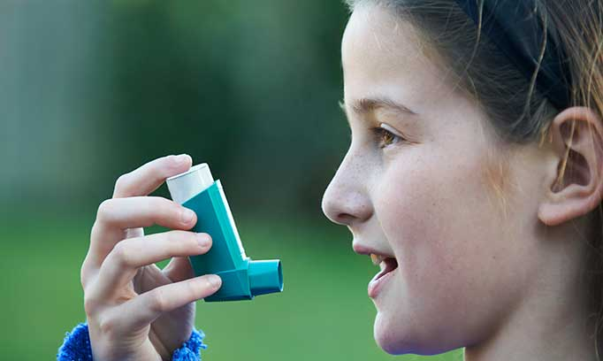 Girl with asthma holds an inhaler near her mouth