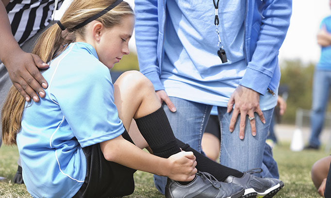 Girl on sidelines with sports injury in kids soccer game
