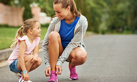 Mother and daughter lacing up tennis shoes