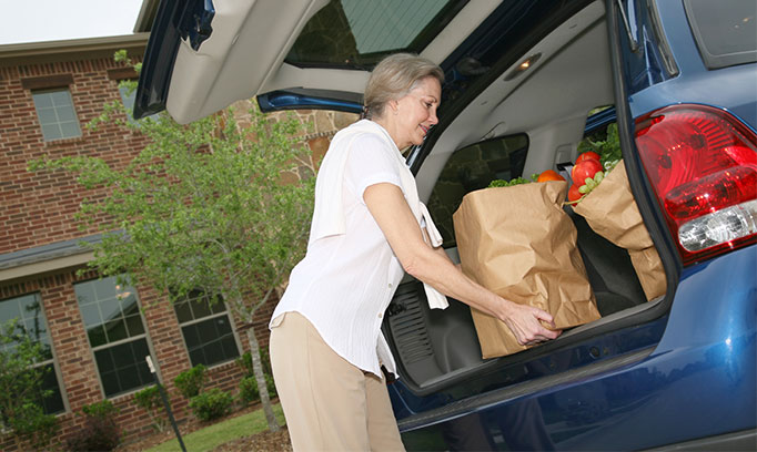 older woman loading groceries into car