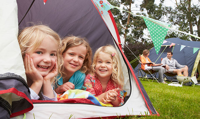 A middle child in a tent with her older and younger sisters