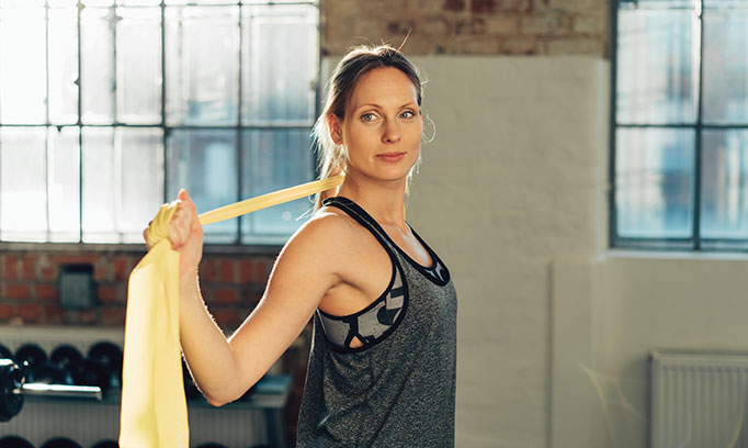 woman at gym with stretchy band for maintaining joint health