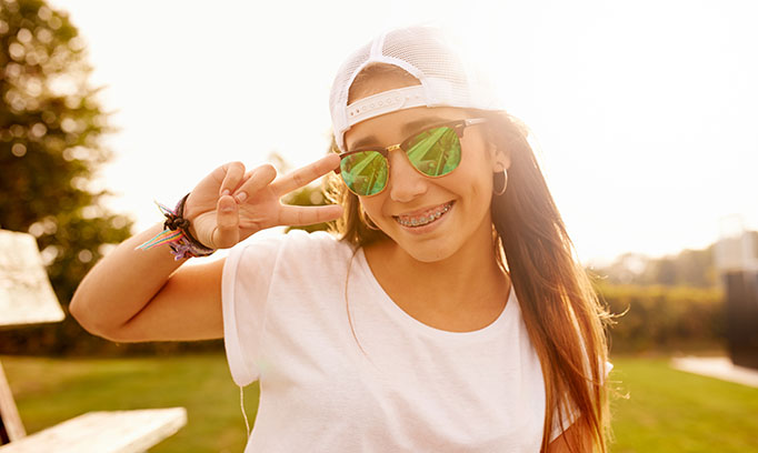 Teenage girl in baseball cap and sunglasses