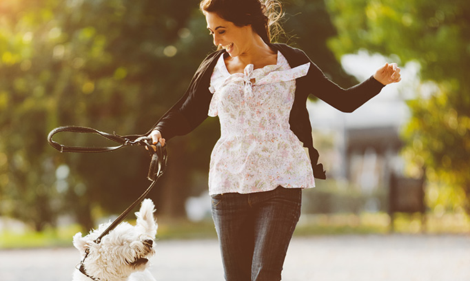 Woman smiling at her dog while out for a walk