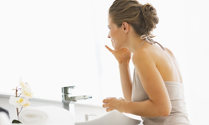Woman applying moisturizer to her face for dry skin.