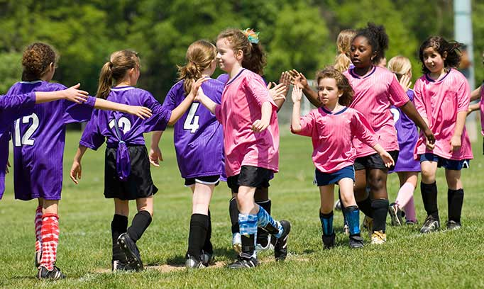 Youth soccer teams high-five each other after a game