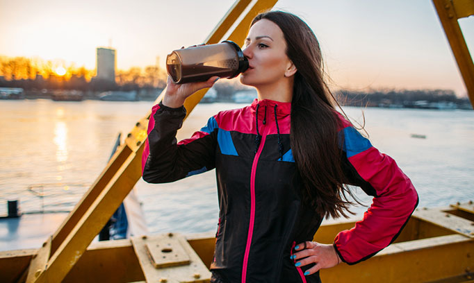 woman shown drinking dark beverage similar to activated charcoal mixture