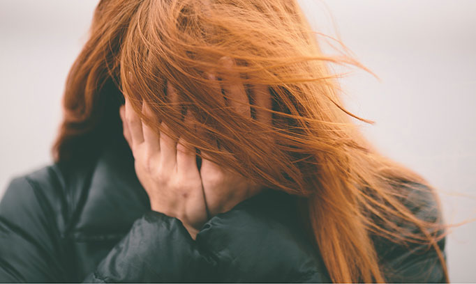 Woman's face is covered by her long red hair and her hands as though unable to face a stressful situation