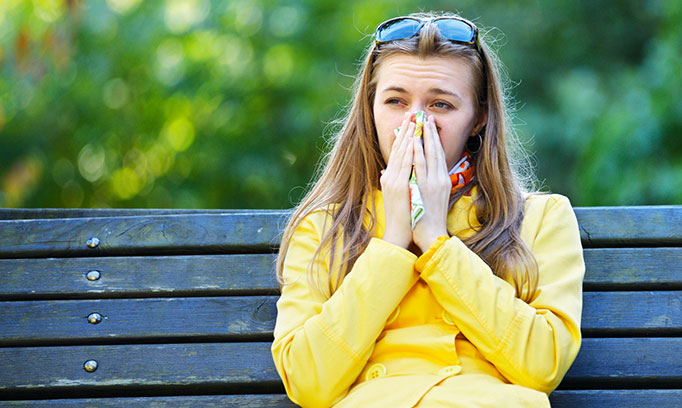 woman blowing nose and wondering if she has a sinus infection