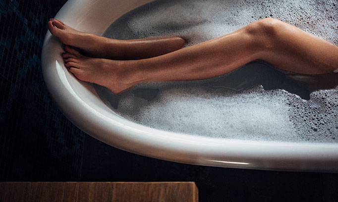 woman's bar legs soaking in bath tub while skipping her workout