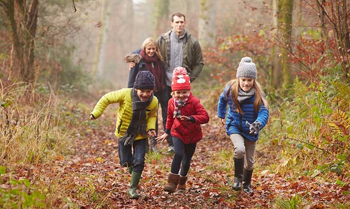 a family of five stays active by running through fall landscape