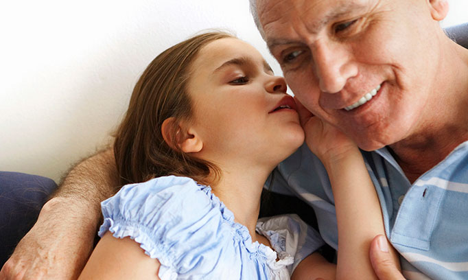Young girl whispers in grandfather's ear to illustrate impact of hearing loss on seniors.