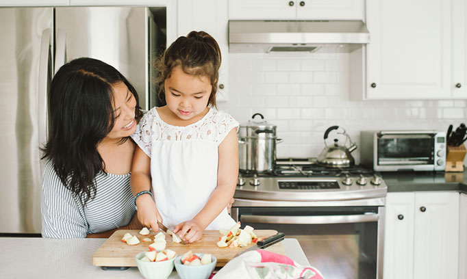 Mom and preschooler enjoy cooking together in kitchen