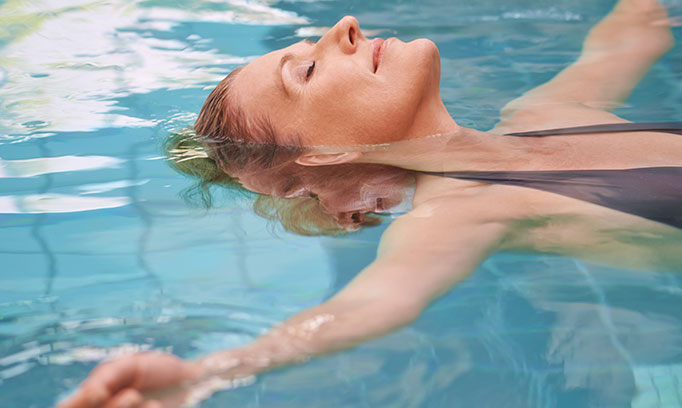 woman floating in pool doing water yoga