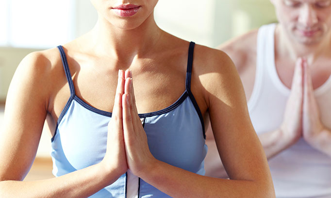 Woman practices yoga, one example of a holistic approach to health