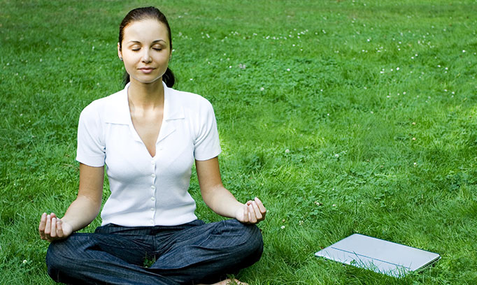 woman seated outside practicing meditation for healthy lifestyle
