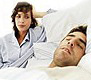 woman sits up in bed and glares and snoring husband who needs sleep apnea treatment