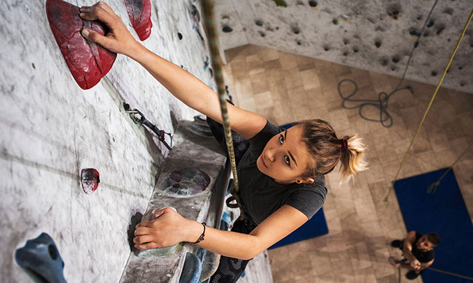 Young woman celebrating Leap Day by climbing an indoor climbing wall.