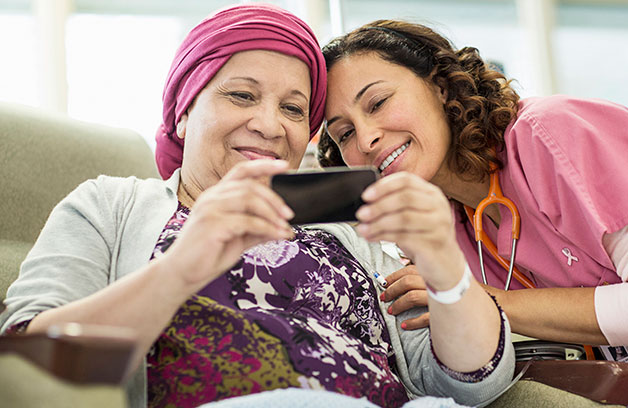 Female cancer patient shows her phone to a female health care professional in pink.
