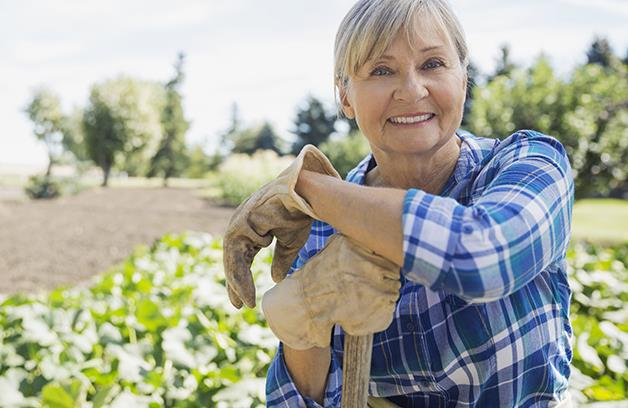 Older female gardener leaning on a shovel handle.