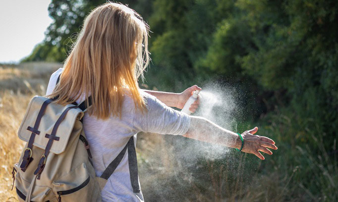 young woman with back pack outdoors spraying her arm to prevent chigger bites 682x408